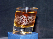 A single slanted shot glass with Julia Ashby Smyth's Ellan Vannin design - full