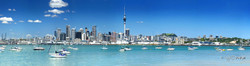 Auckland City at Play' Auckland, New Zealand cityscape showing the city skyline over blue waters.