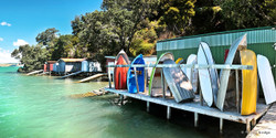 Rocky Bay Boatsheds, Waiheke Island, NZ - panoramic landscape photo print for sale by Lucy G