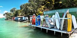 Rocky Bay Boatsheds, Waiheke Island, NZ - panoramic landscape photo print for sale by Lucy G