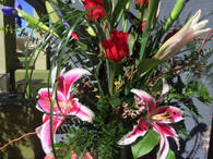 Extra fancy stargazer and Iris and red rose bouquet.  Very tall with special touches and a ti leaf wrapped vase