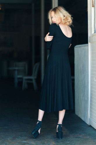 Black knit midi dress with long sleeves and a low back. Button details at the shoulders. Made in the USA by evangeline clothing.