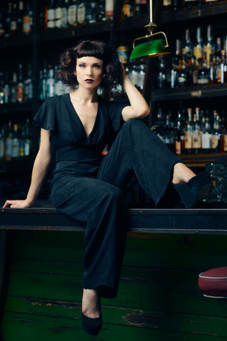 Black jumpsuit with a 40's inspired plunging neckline and flutter sleeves.  Made in the USA by evangeline clothing.
