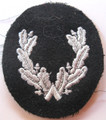 WW2 German Feuerwehr (Fire Police) Sleeve Insignia for an assistant Kreisleter (County Leader). A light grey machine embroidered wreath on a midnight blue wool oval. Worn on the lower left sleeve, this insignia denoted a position, not rank and was created during the war.