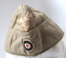 The tropical overseas cap was based on the standard continental overseas cap but in a sand colored cotton material. Tropical overseas caps were sometimes piped in the same manner as the continental style overseas caps, with no piping for EM/NCO ranks, silver piping for officer's ranks and gilt piping for general officer's ranks. The example offered here is made of lightweight, ribbed, tan cotton twill construction and features fold down side and back panels with gently sloping, downward scallops to the front and forward sides.