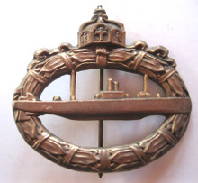 The U-boat War Badge was originally instituted during the First World War on February 1, 1918. It was awarded to recognize U-boat crews who had completed three war patrols. The badge was worn on the lower left side of the uniform and was oval shaped resembling a wreath of laurel leaves. A submarine lay across the center and the German State Crown (Reichskrone) was inlaid at the top center of the wreath.