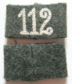 "WW2 German Army 112 Infantry Regt. EM / NCO Shoulder Strap Slides, Pair. Field-grey wool construction slip on shoulder strap slides with a machine stitched seam to the reverse and white chain stitched numerals ""112"" to the obverse.  Slip on shoulder strap slides for wear by enlisted personnel were introduced in January, 1940 for economic and security reasons. The slides were cheaper and easier to produce then full shoulder straps and could be easily changed if an individual was transferred or removed in the field to conceal unit designations. The shoulder strap slides generally had a unit numeral or specific designation letter chain stitched in the appropriated waffenfarbe (Branch of Service Color). In 1943 all embroidery was changed to gray, reflecting the shortage of dyes, materials and difficulty of keeping up with the constant reorganization of units as the war progressed.  Infantry Regiment 112 was part of the 38th Division and served in Den Haag (Netherlands) and became Grenadier Regiment 112 in October 1942.  Pair. Exc."