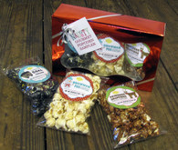 "Each ""Naughty"" Gourmet Holiday Popcorn Gift Box comes with one ""Lump O' Coal"" Black Cherry popcorn stocking stuffer, one ""Snowman Poo"" Vanilla popcorn stocking stuffer, and one ""Reindeer Droppings"" Cocoa popcorn stocking stuffer in a metallic red gift box with a gift tag."