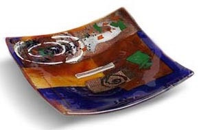 3.5 inch square blue glass platter featuring red and brown fused glass, touches of green and other colors and a white spiral