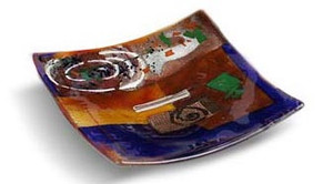 6 inch square blue glass platter featuring red and brown fused glass, touches of green and other colors and a white spiral