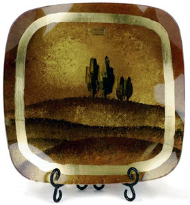 A fused glass square platter featuring earth tones, hills and trees on the horizon.  A gold band around the perimeter adds detail