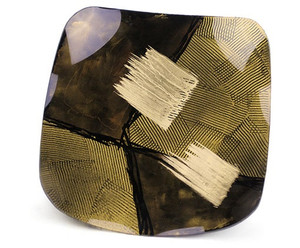 A square fused glass platter featuring brown and yellow, with some white, all with a combing pattern, finished with two bold metallic gold strokes