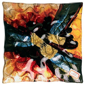 """A 12"""" square fused glass plate featuring multiple colors and shapes, including yellow, red, blue and black with hand painted metallic gold details in the center"""