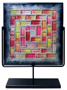 A 17 inch decorative glass square panel featuring grey in the background with red, yellow and clear glass tiles fused in a pattern