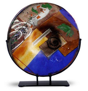 """15"""" round fused glass platter featuring blue, yellow, red glass, with abstract designs and a white spiral"""