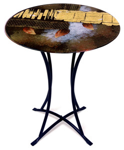 A fused glass table featuring black, gold, white with some red leaf-like splotches and a bold gold stripe