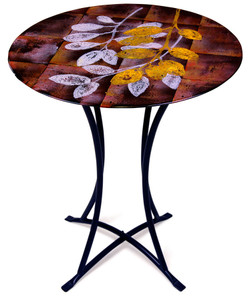 Geometric patterns in black yellow and red are the backdrop for the leaves on this fused glass cafe table