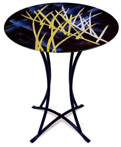 This round fused glass cafe table features a muted black and blue geometric background, with artful strokes of white and gold representing the wind