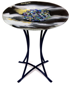 A fused glass cafe table featuring black and white, with a multi-color marble look in its center