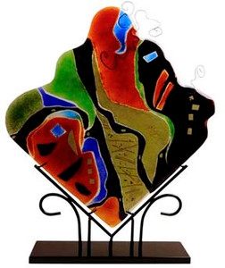A decorative fused glass panel, in a diamond shape, with many bold colors.  Abstract.  Stand included.