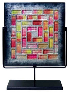 A square fused glass panel featuring red and pink mosaic-like tiles surrounded by black.  Stand included