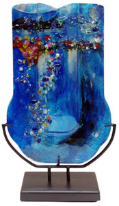 Marine blue colors are featured in this 18-inch tall U-shaped fused glass bud vase with many other colored pieces fused in place.  Metal stand included.
