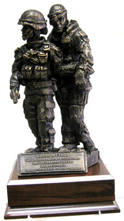 """Awesome military statue of a female service member assisting a wounded warrior mounted on a 6.5""""W x 6.5""""D x 1-3/4""""H laminated wood base.  Total height is 12"""". Warrior ethos is shown on the front."""