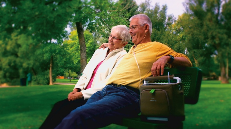 SimplyGo-portable-oxygen-concentrator-couple-on-bench.jpg