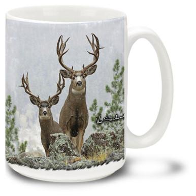 Two Huge Mule Deer Bucks standing against a snowy backdrop.