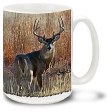 Whitetail Buck standing on high prairie grass.