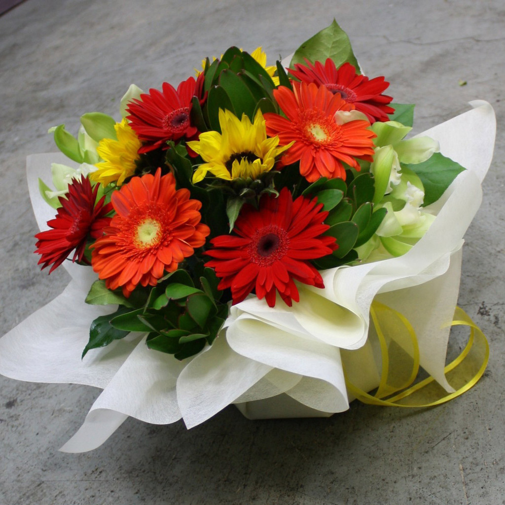 Full of bright red, yellow and orange gerberas with sunflowers and lime green accents. Arranged in a box.