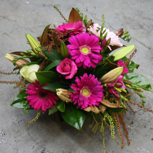 Oriental lilies, gerberas, roses and assorted seasonal foliage create a vibrant bowl arrangement.