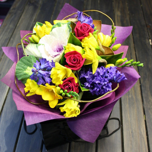 Seasonal carry bag arrangement of scented pink, yellow and blue blooms.