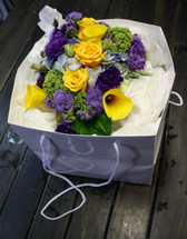 Purples, yellows and blues inc lisianthus, callas and yellow roses with assorted foliage in a carry bag.