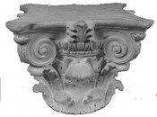 This round cast gypsum column capital features acanthus leaves and corner volutes with a round base