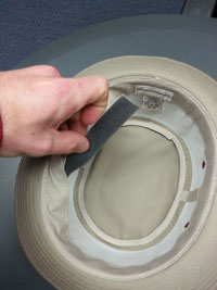Inserting Hat Sizing tape under hat band