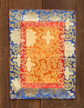 Small orange table brocade with red and blue border (12x19 inches)