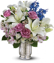 Make her dreams come true with this ethereal bouquet. Beautiful snow-white lilies, lavender roses and a bright blue hint of delphinium create a dreamy declaration of your affection she'll never forget.  Vase may vary.