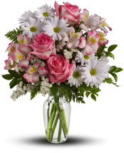 Opening the door to a surprise bouquet is one of life's happiest experiences. Give it to someone special with this delightful array of pink roses, pink alstromeria, white mums and white statice in a sparkling glass vase. They'll be talking about it for days.