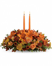 Graciously gather your family around the warm glow and classic autumn colors of this stunning Thanksgiving centerpiece. A lush variety of burnt orange blooms are gathered under a pair of tall, graceful candles - perfect for decorating your Thanksgiving dinner table, entryway or hearth. •Fall flowers include orange roses, orange asiatic lilies, dark orange alstroemeria, bronze button mums, yellow cushion mums, rust cushion mums, green oregonia and green huckleberry.  •Accented with oak leaves and two orange taper candles. •Orientation: All-Around