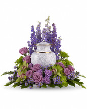 As you come together to share your memories, these assorted purple flowers cradle the urn in a loving embrace. The soft greens and soothing purples are ideal to grace a memorial service. Includes lovely flowers such as lavender larkspur, roses, carnations and asters, and fuji chrysanthemums.Please note: Arrangement does not include urn.