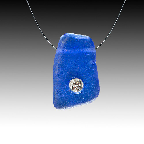 A cobalt piece of genuine beach glass hung delicatley on an invisible chain with a 10 pt diamond set right into it!