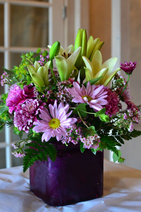 A glass purple square vase filled with lavender daisies, lavender poms, white lilies, fuchsia carnations