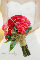 Hombre style bridal bouquet in a tight clutch with Coral roses and Deep coral carden roses with an accent of Gold seeded eucaliptis and Gold curly will to give it a textural quality. Wrapped in a gold Mesh ribbon. Perfect for the modern bride on her wedding day.