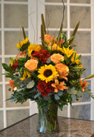 A large show stopper! A clear vase filled with cattails, sunflowers, curly willow, mums, lilies & roses