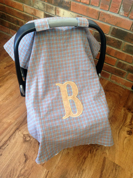 This car seat cover is gray and tan checkered on the front, with some hints of red and navy. The inside is lined with a soft, white minky fabric. Add a name or monogram for a personal touch! The personalization will be placed in the center of the cover.