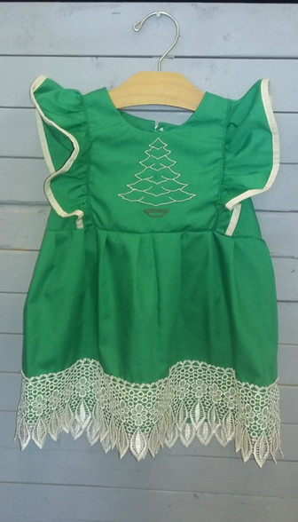 This adorable dress is perfect for Christmas. It has a monogrammed Christmas tree on the front and gorgeous lace at the bottom.