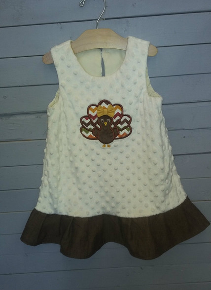 This is a cream minky dress, with turkey applique. It is very soft and warm and has a brown ruffle at the bottom. Perfect for the holidays.