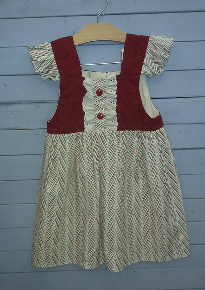 This gorgeous pinafore dress is perfect for the holidays! The Christmas colors correspond so well! The eyelet in the middle brings it all together!