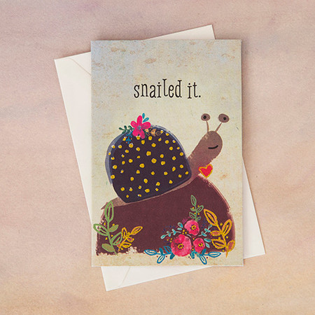 """A super punny snail """"Snailed It"""" featuring gold glitter details! Perfect for graduates, new jobs or to celebrate just about anything! Packaged individually in a cello bag with envelope. Cards are blank inside for personal message.  5.25in L x 3.5in W"""